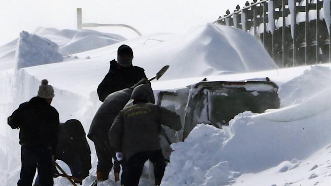 In this photo taken Sunday, March 3, 2013, policemen shovel snow around a vehicle of Kazuyo Miyashita along a road in Nakashibetsu, Hokkaido, northern Japan. Kyodo news service says Miyashita and her three children died at a hospital Saturday night of carbon-monoxide poisoning after the vehicle got buried in the snow. Heavy snow that fell on the main northern Japanese island of Hokkaido over the weekend has killed eight people, including the family. (AP Photo/Hokkaido Shimbun Press via Kyodo News) JAPAN OUT, MANDATORY CREDIT, NO LICENSING IN CHINA, HONG KONG, JAPAN, SOUTH KOREA AND FRANCE