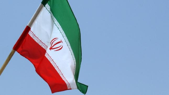 The Iranian flag flutters over the reactor building at the Russian-built Bushehr nuclear power plant in southern Iran