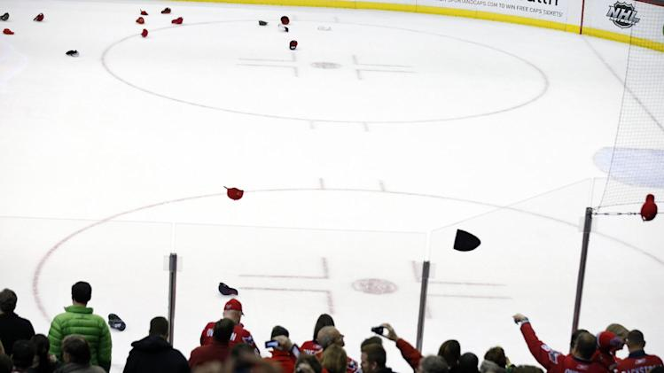 Hats fly on the ice after Washington Capitals right wing Alex Ovechkin, of Russia, scored his third goal of the game for a hat trick, in the second period of an NHL hockey game against the Tampa Bay Lightning, Tuesday, Dec. 10, 2013, in Washington. (AP Photo/Alex Brandon)
