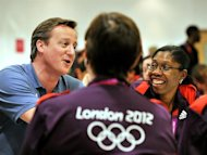 Britain's Prime Minister David Cameron (L) speaks to a group of Olympic volunteers at The ExcCel venue in Docklands, east London on August 8, 2012, during The 2012 London Olympic Games.  AFP PHOTO/John STILLWELL/POOL