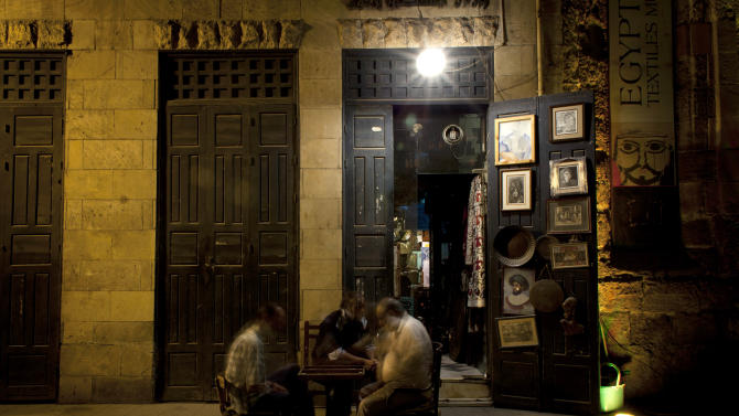 In this photo taken Sunday, May 12, 2013, Egyptian souvenir shop owners pass time playing a traditional game as they wait for customers on El-Moez Street of the historical Fatimid Cairo, Egypt. Cairo, the Arab world's most populated city, is often referred to as an open-air museum of Islamic antiquities and the city of 1,000 minarets. But its rich history and contributions to Islamic art has languished. (AP Photo/Nasser Nasser)