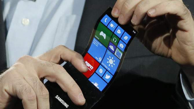 Eric Rudder, chief technical strategy officer of Microsoft, holds a prototype Windows smartphone with a flexible OLED display during Samsung's keynote address at the International Consumer Electronics Show in Las Vegas, Wednesday, Jan. 9, 2013. (AP Photo/Jae C. Hong)