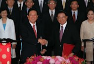 Chen Yunlin, left, chairman of China's Association for Relations Across the Taiwan Straits, shakes hands with Chiang Pin-kung, chairman of Taiwan's Straits Exchange Foundation, after exchanging documents signed an investment protection pact at a Taipei hotel, Taiwan, Thursday, Aug. 9, 2012. Taiwan and China signed the pact Thursday, another step on the road to closer business ties that so far seems to be falling short of promises to energize Taiwan's sputtering economy. (AP Photo/Chiang Ying-ying)
