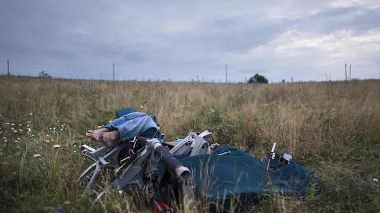 A body sitting in a plane chair is placed at the crash site of a Malaysia Airlines jet near the village of Hrabove, eastern Ukraine, Saturday, July 19, 2014. World leaders demanded Friday that pro-Russia rebels who control the eastern Ukraine crash site of Malaysia Airlines Flight 17 give immediate, unfettered access to independent investigators to determine who shot down the plane. (AP Photo/Evgeniy Maloletka)