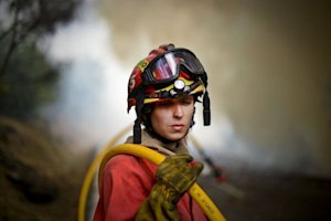 A firefighter holds a hose in front a wildfire around…