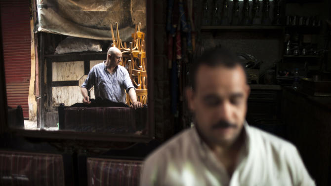 An Egyptian man is seen reflected on a mirror of his coffee shop in the Khan El-Khalili market, normally a popular tourist destination, in Cairo, Egypt, Wednesday, Aug. 21, 2013. Riots and killings that erupted across the country after the crackdown against followers of ousted President Mohammed Morsi have delivered a severe blow to Egypt's tourism industry, which until recently accounted for more than 11 percent of the country's gross domestic product and nearly 20 percent of its foreign currency revenues. (AP Photo/Manu Brabo)