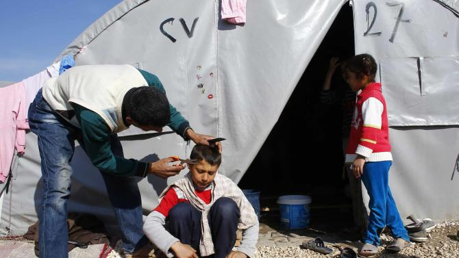 A Kurdish refugee man from the Syrian town of Kobani cuts his son's hair at a refugee camp in the border town of Suruc