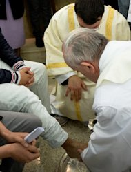 In this photo provided by the Vatican newspaper L'Osservatore Romano, Pope Francis, with back to camera at right, washes the foot of an inmate at the juvenile detention center of Casal del Marmo, Rome, Thursday, March 28, 2013. Francis washed the feet of a dozen inmates at a juvenile detention center in a Holy Thursday ritual that he celebrated for years as archbishop and is continuing now that he is pope. Two of the 12 were young women, an unusual choice given that the rite re-enacts Jesus' washing of the feet of his male disciples. The Mass was held in the Casal del Marmo facility in Rome, where 46 young men and women currently are detained. Many of them are Gypsies or North African migrants, and the Vatican said the 12 selected for the rite weren't necessarily Catholic. (AP Photo/L'Osservatore Romano, ho)