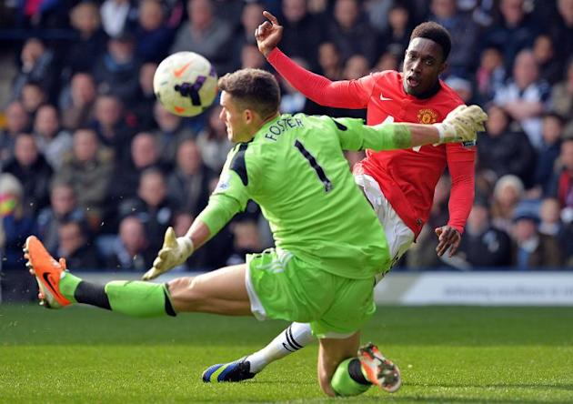 Manchester United's striker Danny Welbeck (R) scores his team's third goal past West Bromwich Albion's goalkeeper Ben Foster during an English Premier League football match at The Hawthorn