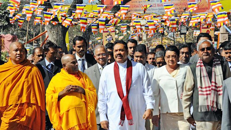 Sri Lankan President Mahinda Rajapaksa, center, along with his wife Shiranthi Rajapaksa visit the Mahabodhi temple in the town of Bodhgaya, believed to be the place where Buddha attained enlightenment, India, Friday, Feb. 8, 2013. Various Tamil groups and leaders are protesting Rajapaksa's visit holding him responsible for the killing of innocent Tamils during the civil war in Sri Lanka. Rajapaksa is on a personal visit to the country. (AP Photo/Manish Bhandari)
