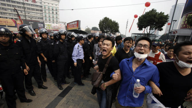Protesters march past Chinese police men in Zhejiang province's Ningbo city, protesting the proposed expansion of a petrochemical factory Sunday, Oct. 28, 2012. Thousands of people in the eastern Chinese city clashed with police Saturday while protesting the proposed expansion of the factory that they say would spew pollution and damage public health, townspeople said. (AP Photo/Ng Han Guan)