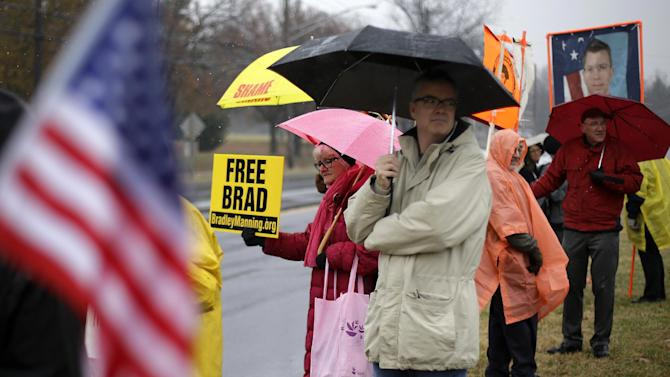 FILE - In this Nov. 27, 2012 file photo, demonstrators stand in support of Army Pfc. Bradley Manning outside of Fort Meade, Md., before a pretrial hearing. The Bradley Manning Support Network does everything from raise funds for Manning's legal defense to coordinate carpools for supporters to get to Manning's court-martial at Fort Meade. It posts sign-waving demonstrators outside the fort's main gate each trial day and tries to fill the 20 courtroom seats reserved for the public and press. (AP Photo/Patrick Semansky, File)