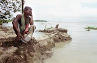 "A Bangladeshi villager sits on an eroding river bank on the Padma River in 2003. Bangladesh on Saturday called a World Bank decision to cancel a $1.2-bn loan to build the nation's biggest bridge -- aimed at transforming the poverty-hit south -- ""a bolt from the blue"""