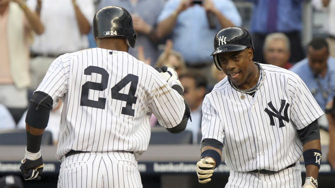 New York Yankees' Curtis Granderson, right, greets Robinson Cano after Cano hit a two-run home run during the first inning of a baseball game against the Baltimore Orioles, Tuesday, July 31, 2012, at Yankee Stadium in New York. (AP Photo/Seth Wenig)