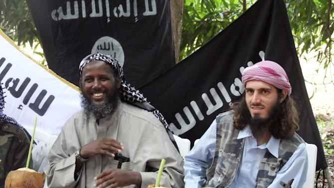 """FILE - In this Wednesday, May 11, 2011 file photo, American-born Islamist militant Omar Hammami, 27, also known as Abu Mansur al-Amriki, right, and deputy leader of al-Shabab Sheik Mukhtar Abu Mansur Robow, left, sit under a banner which reads """"Allah is Great"""" during a news conference of the militant group at a farm in southern Mogadishu's Afgoye district in Somalia. A 50-member group of U.S. government workers comprised of Americans and foreign nationals called the Digital Outreach Team is countering extremist propaganda on sites like Twitter and Facebook, with the top official on the team, Alberto Fernandez, saying the goal is to contest space that had previously been ceded to extremists. (AP Photo/Farah Abdi Warsameh, File)"""