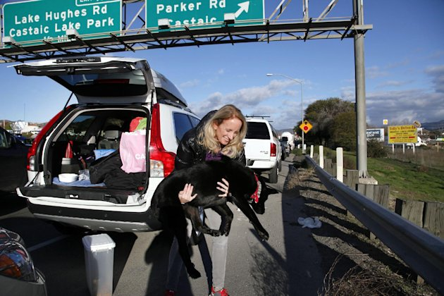 Heidi Blood carries her dog to the side of the road for a drink of water while waiting in line with her car along Interstate 5 north of Los Angeles on Friday, Jan. 11, 2013. The California Highway Pat