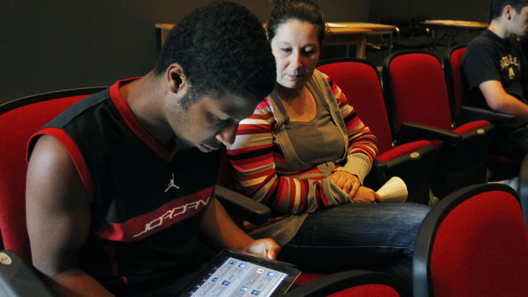 In this Aug. 23, 2011 photo, sophomore Lenny Thelusma, 16, checks out his new iPad as his mother, Tara Killion, looks on at Burlington High School in Burlington, Mass. Burlington is giving iPads this year to every one of its 1,000-plus high school students. Some classes will still have textbooks, but the majority of work and lessons will be on the iPads. (AP Photo/Elise Amendola)