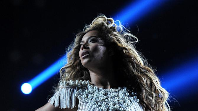 """IMAGE DISTRIBUTED FOR PARKWOOD ENTERTAINMENT - Singer Beyonce performs on her """"Mrs. Carter Show World Tour 2013"""" at Staples Center on Monday, July 1, 2013, in Los Angeles. Beyonce is wearing a custom hand beaded peplum one-piece by Ralph & Russo with shoes by Stuart Wieztman. (Photo by Frank Micelotta/Invision for Parkwood Entertainment/AP Images)"""