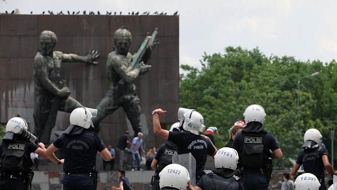 Police chase protesters as Turkish riot police spray water cannon at demonstrators who remained defiant after authorities evicted activists from an Istanbul park, making clear they are taking a hardline against attempts to rekindle protests that have shaken the country, in city's main Kizilay Square in Ankara, Turkey, Sunday, June 16, 2013.(AP Photo/Burhan Ozbilici)