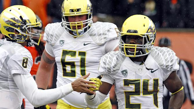Oregon running back Kenjon Barner, right, is congratulated on his touchdown by quarterback Marcus Mariota during the first half of their NCAA college football game against Oregon State in Corvallis, Ore., Saturday, Nov. 24, 2012.  In the background is Oregon's Nick Cody.(AP Photo/Don Ryan)