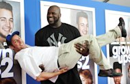Former professional basketball player Shaquille O'Neal gives actor Adam Sandler a lift at the premiere of