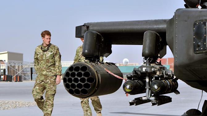 Britain's Prince Harry, left,  is shown the Apache helicopter by a member of his squadron (name not provided) at Camp Bastion in Afghanistan, Friday Sept. 7, 2012. Prince Harry will be based at Camp Bastion during his tour of duty as a co-pilot gunner, returning to Afghanistan to fly attack helicopters in the fight against the Taliban. (AP Photo/John Stillwell)
