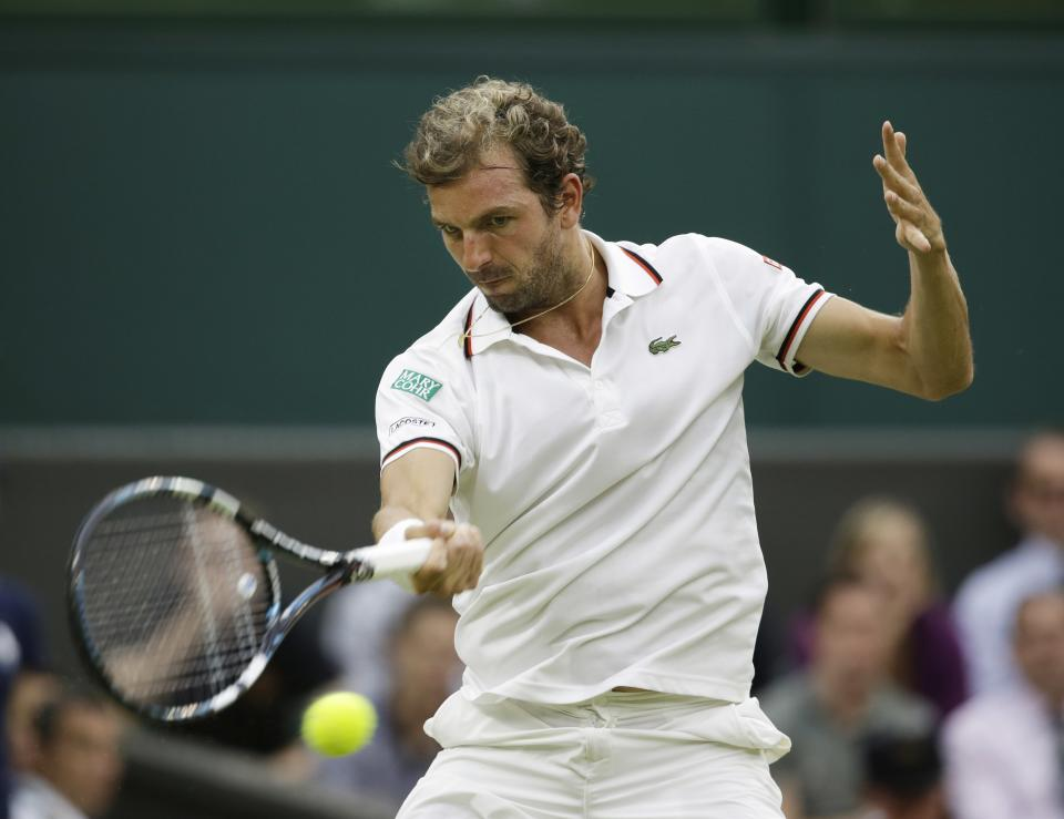 Julien Benneteau of France returns a shot to Roger Federer of Switzerland during a third round men's singles match at the All England Lawn Tennis Championships at Wimbledon, England, Friday, June  29, 2012. (AP Photo/Alastair Grant)