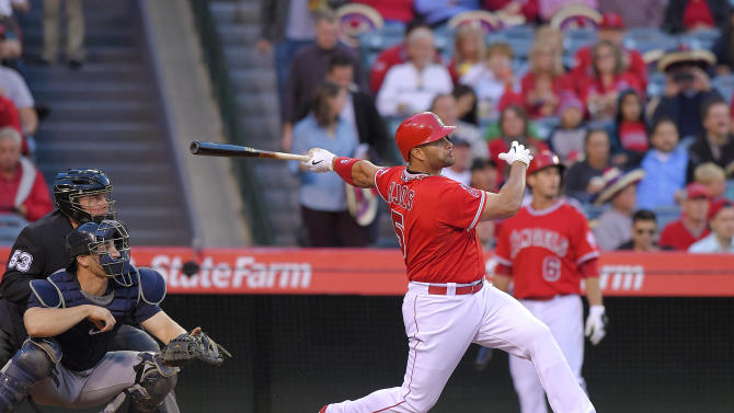 Los Angeles Angels' Albert Pujols hits a two-run home run as Seattle Mariners catcher Mike Zunino, center, and home plate umpire Greg Gibson watch during the first inning of a baseball game, Tuesday, May 5, 2015, in Anaheim, Calif. (AP Photo/Mark J. Terrill)