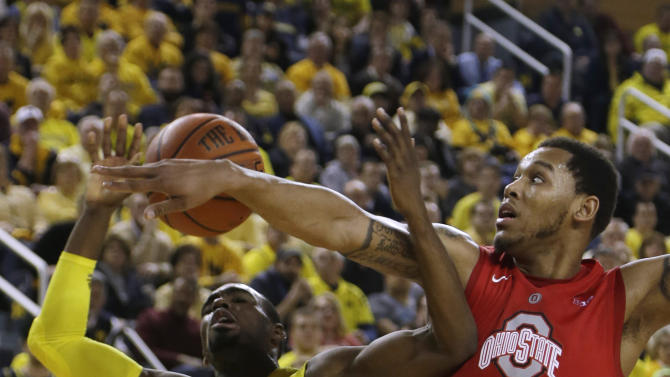 Ohio State center Amir Williams (23) knocks the ball away from Michigan guard Tim Hardaway Jr. (10) during the second half of an NCAA college basketball game at the Crisler Center in Ann Arbor, Mich., Tuesday, Feb. 5, 2013. Michigan won 76-74 in overtime. (AP Photo/Carlos Osorio)