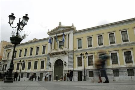 Commuters walk in front of the old headquarters of National Bank in Athens