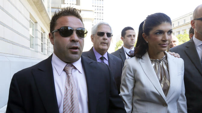"""FILE - In this July 30, 2013 file photo, """"The Real Housewives of New Jersey"""" stars Giuseppe """"Joe"""" Giudice, left, and his wife, Teresa Giudice, of Montville Township, N.J., walk out of Martin Luther King Jr. Courthouse after an appearance in Newark, N.J. The Giudices are facing additional fraud charges as they were each indicted Monday, Nov. 18, 2013, on one count of bank fraud and one count of loan application fraud. Monday's charges are in addition to a 39-count indictment handed down in July, charging the couple with conspiracy to commit mail and wire fraud, bank fraud, making false statements on loan applications and bankruptcy fraud. (AP Photo/Julio Cortez, File)"""