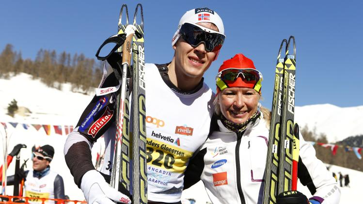 Finland's Roponen, winner of the women's competition poses together with Norway's Gloeersen, winner of the men's competition after the 46th Engadin Ski Marathon in the village of S-chanf