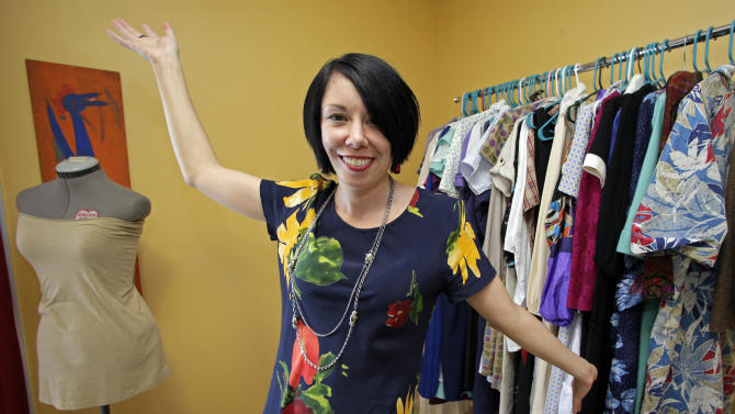 """In this July 16, 2014 photo, Jillian Owens poses with some of her thrift store dresses at her home in Columbia, S.C. Since 2010, the 32-year-old Columbia resident has been delving into thrift store racks around the area, taking what some may see as """"ugly"""" pieces and whipping them into hip, trendy fashions. (AP Photo/Chuck Burton)"""