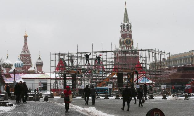 Workers disassemble a Louis Vuitton pavilion a Louis Vuitton pavilion which is in the shape of a giant suitcase, with St. Basil's Cathedral (L) and the Spasskaya Tower (R) in Red Square near the K