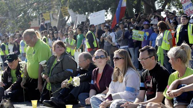 Protestors sit outside the Walmart store Friday Nov. 23, 2012 in Paramount, Calif. Wal-Mart employees and union supporters are taking part in today's nationwide demonstration for better pay and benefits A union-backed group called OUR Walmart, which includes former and current workers, was staging the demonstrations and walkouts at hundreds of stores on Black Friday, the day when retailers traditionally turn a profit for the year. ( AP Photo/Nick Ut)