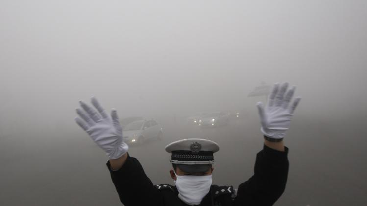 A traffic policeman signals to drivers during a smoggy day in Harbin