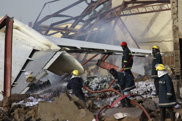 Rescue workers search for bodies at the site of a plane crash in Lagos, Nigeria, Monday, June 4, 2012. A passenger plane carrying more than 150 people crashed in Nigeria's largest city on Sunday, gove