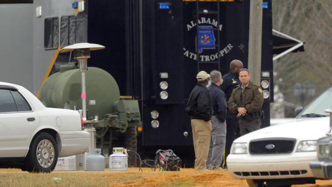 FBI and other personnel process the crime scene in Midland City, Ala. Tuesday, Feb. 5, 2013, a day after a police raid left Jimmy Lee Dykes dead. Dykes held a a 5-year-old boy hostage for a week in an underground bunker on the property. Authorities painstakingly checking for bombs on the abductor's property Tuesday.  (AP Photo/al.com, Joe Songer) MAGS OUT