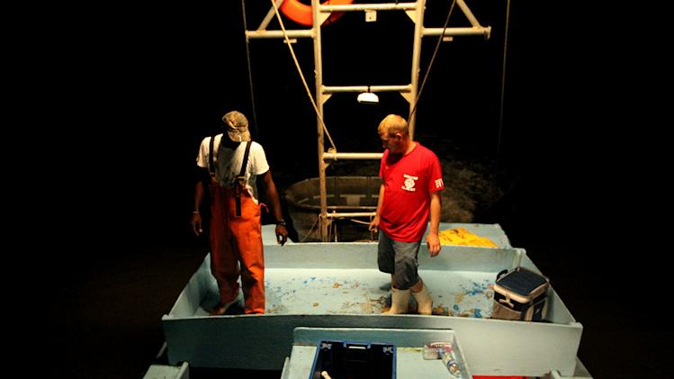 "Captain Dardar and a deck hand assess the nights catch as seen on ""Ragin' Cajuns."""