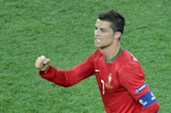 Portuguese forward Cristiano Ronaldo celebrates after scoring during the Euro 2012 football championships match Portugal vs. Netherlands, on June 17, 2012 at the Metalist stadium in Kharkiv.        AFP PHOTO / SERGEI SUPINSKY