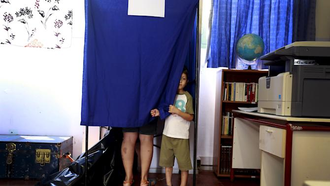 A boy peeks out of an voting booth in the village of Meyisti