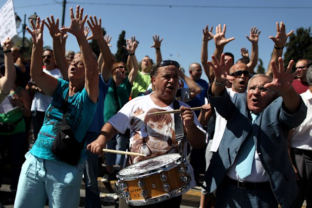 Protesters gestures towards the Greek Parliament during a nationwide general strike in Athens, Wednesday, Sept. 26, 2012.  Police clashed with protesters hurling petrol bombs and bottles in central At