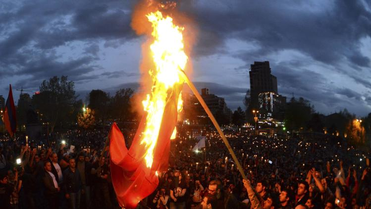 Demonstrators set fire to a Turkish flag during a torch-bearing march marking anniversary of 1915 mass killings of Armenians in Ottoman Empire, in Yerevan