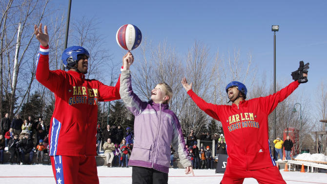 IMAGE DISTRIBUTED FOR HARLEM GLOBETROTTERS - The Harlem Globetrotters seen at Globetrotters Play Basketball On Ice on Monday, Jan. 7, 2013 in Portage, MI. Harlem Globetrotter Scooter Christensen (l) spins the ball on the finger of 10-year old Emilee Bogda of Kalamazoo, MI. Handles Franklin (r) leads the cheers.  The Globetrotters took to the ice to help fill the void of the cancelled Winter Classic in Michigan. (Photo by William Pugliano/Invision for Harlem Globetrotters/AP Images)