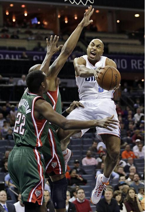Charlotte Bobcats' Gerald Henderson, right, drives against Milwaukee Bucks' Khris Middleton, left, during the first half of an NBA basketball game, Monday, Dec. 23, 2013, in Charlotte, N.C