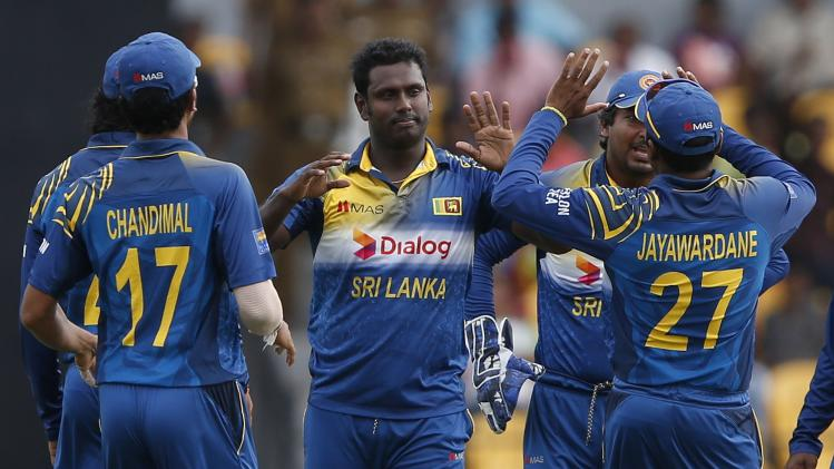 Sri Lanka's captain Mathews celebrates with teammates after taking the wicket of Pakistan's Hafeez during their first ODI cricket match in Hambantota