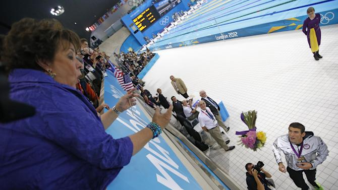 FILE - In this Aug. 4, 2012, file photo, Michael Phelps, of the United States, throws flowers to his mother Debbie after winning gold in the men's 4x100-meter medley swimming relay at the Aquatics Centre in the Olympic Park during the 2012 Summer Olympics in London. Phelps has added another triumph to his list of accomplishments: The Associated Press male athlete of the year, Thursday, Dec. 20, 2012.(AP Photo/Jae C. Hong, File)