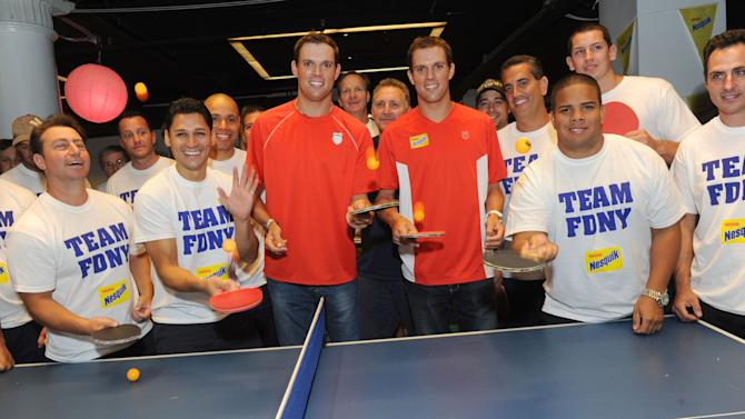 COMMERCIAL IMAGE - Gold medalists and champion tennis players Bob, center left, and Mike Bryan, center right, greet members of the FDNY before the Nesquik FDNY Foundation Charity Ping Pong tournament at SPiN Galactic in New York, Thursday, Aug. 23, 2012.  The Bryan Brothers took on FDNY's ace ping pong players to pay tribute  to and support the FDNY.  (Diane Bondareff/Invision for Nesquik/AP Images)