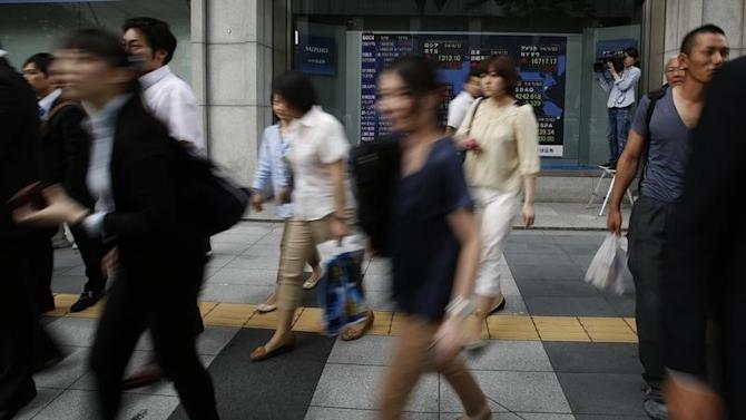 Pedestrians walk past at an electronic board outside a brokerage in Tokyo