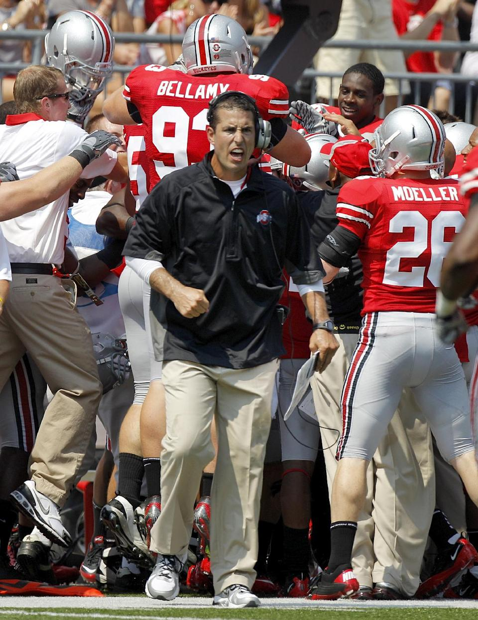 Ohio State head coach Luke Fickell reacts toward the field as his players pile on linebacker Andrew Sweat behind him after Sweat intercepted a pass from Akron quarterback Clayton Moore during the second quarter of an NCAA college football game in Columbus, Ohio on Saturday, Sept. 3, 2011.  (AP Photo/Amy Sancetta)